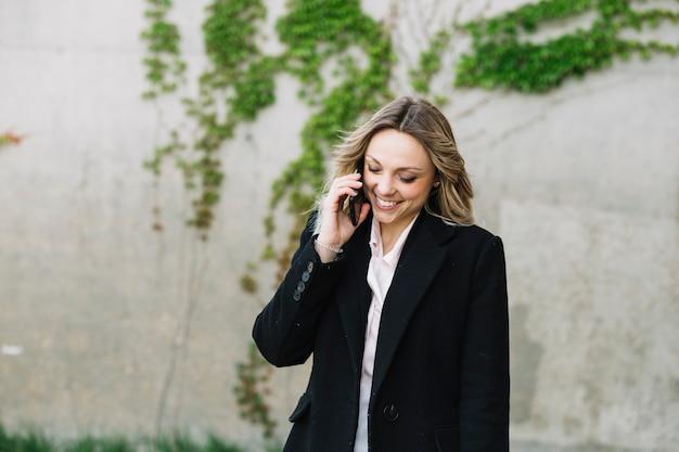 Businesswoman podejmowania rozmowy telefonicznej na zewnątrz