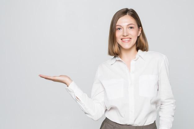 Businesswoman pokazując miejsce na kopię produktu z otwartą dłonią. uśmiechnięty przyjazny wyraz na młodej bizneswoman w okularach na białym tle na białej ścianie.