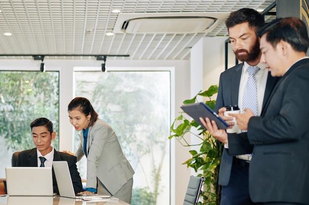 Businesswoman pomaga współpracownikowi z raportem, gdy jej dwóch koleżanek omawia informacje na komputerze typu tablet