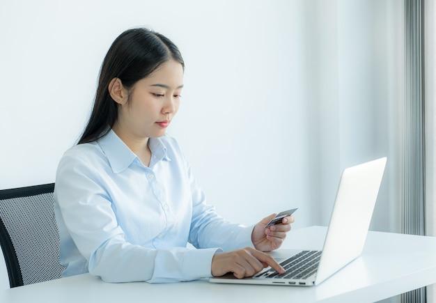 Businesswoman posiadania i używania karty kredytowej do zakupów online z domu za pomocą laptopa, płatności e-commerce, bankowości internetowej, wydawania pieniędzy na następne wakacje.
