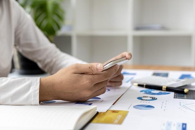 Businesswoman posiadania telefonu komórkowego, ona patrzy na informacje na telefon komórkowy, które oficer finansowy wysyła za pośrednictwem programu do przesyłania wiadomości online. koncepcje finansowe.