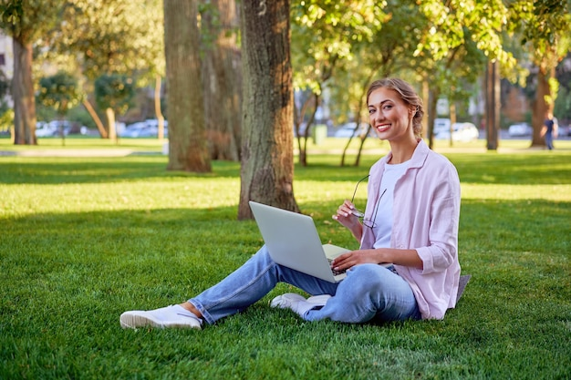 Businesswoman posiedzenia trawa lato park za pomocą laptopa biznes osoba pracująca zdalnie. na wolnym powietrzu