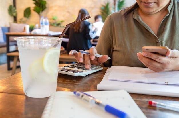 Businesswoman pracy na kalkulatorze i telefon komórkowy z lglass napoju cytrynowego.