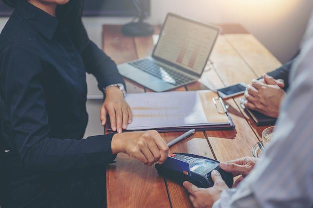 Businesswoman przesuwając kartę kredytową przez czytnik kart kredytowych