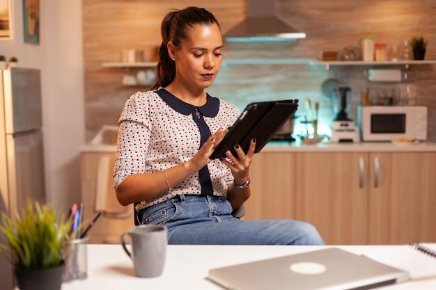 Businesswoman przy użyciu komputera typu tablet podczas pracy z domowej kuchni. pracownik korzystający z nowoczesnych technologii o północy wykonujący nadgodziny w pracy, firmie, zajęty, karierze, sieci, stylu życia, bezprzewodowo.
