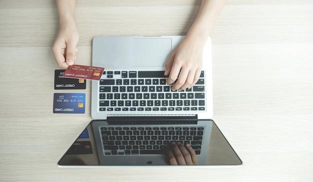 Businesswoman ręcznie wpisując laptopa i przytrzymaj kartę kredytową na zakupy online na komputerze z domu, płatności e-commerce, bankowość internetowa, wydawanie pieniędzy.