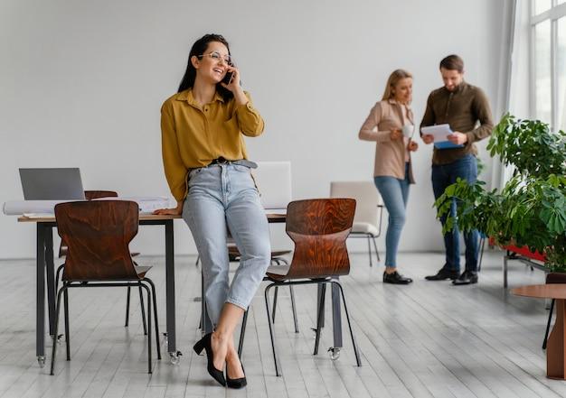 Businesswoman rozmawia przez telefon, podczas gdy jej koledzy z drużyny rozmawiają