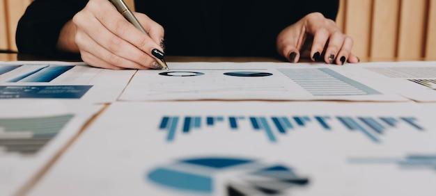 Businesswoman siedzi przy biurku w biurze, sprawdzanie i analizowanie raportu. rachunkowość, pióro w ręku na wykresie