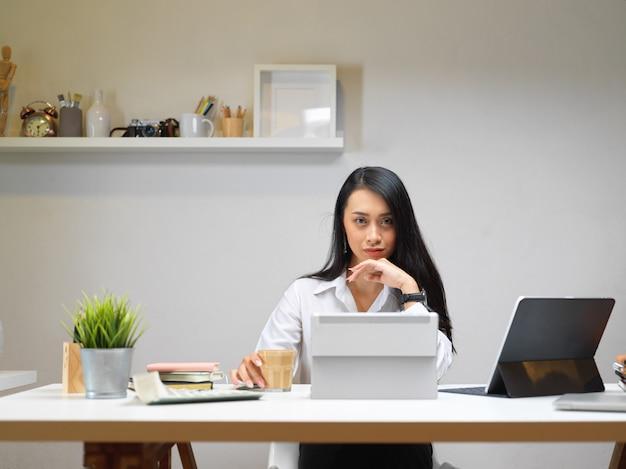 Businesswoman siedzi przy biurku z kawą