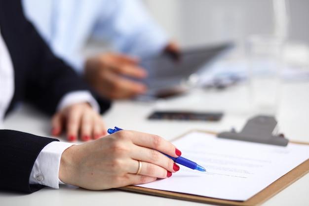 Businesswoman siedzi w biurze, pisząc na dokumenty