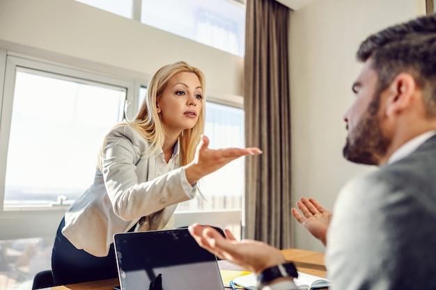 Businesswoman stojąc w biurze i nie zgadzając się z kolegą, który siedzi w eleganckich ubraniach przed laptopem. problemy w pracy, niezgoda