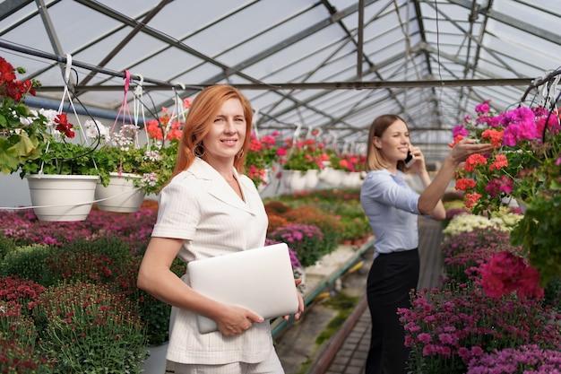 Businesswoman stwarzających z laptopem, podczas gdy jej partner omawia przez telefon propozycję w zielonym domu z kwiatami.