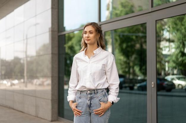 Businesswoman sukcesu kobieta biznes osoba stojąca na zewnątrz korporacyjnego budynku zewnątrz. kaukaski pewność siebie profesjonalny biznes kobieta średni wiek kobieta biała koszula duże okno