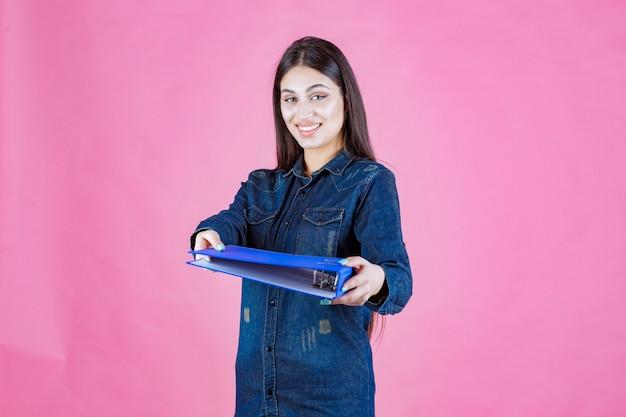Businesswoman trzyma niebieski folder oferując go swojemu koledze