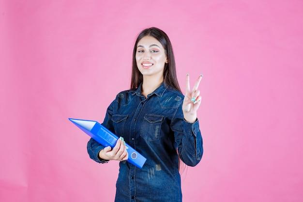 Businesswoman trzymając niebieski folder i wysyłając znak pokoju