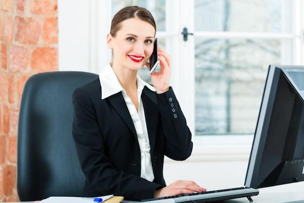 Businesswoman w biurze siedzi na komputerze