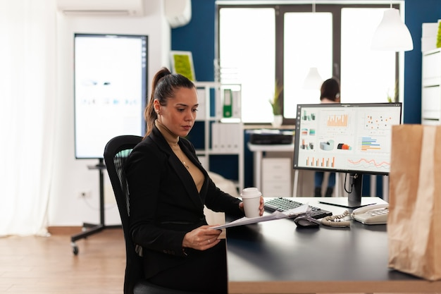 Businesswoman w korporacyjnym uruchamianiu biura analizującego dokumenty, wykres patrząc na schowek. torba papierowa z recyklingu z pysznym, smacznym jedzeniem na przerwę obiadową. pracownik posiadający filiżankę kawy.