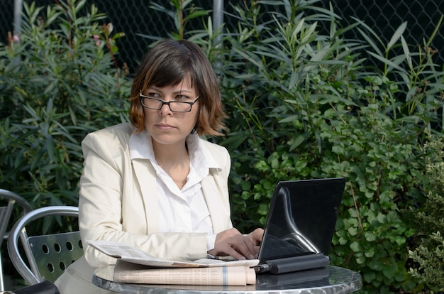 Businesswoman w okularach siedzi przy stole na świeżym powietrzu ze swoim laptopem