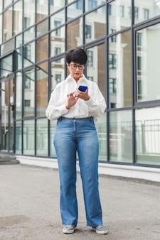 Businesswoman wpisując na jej telefon komórkowy długi widok