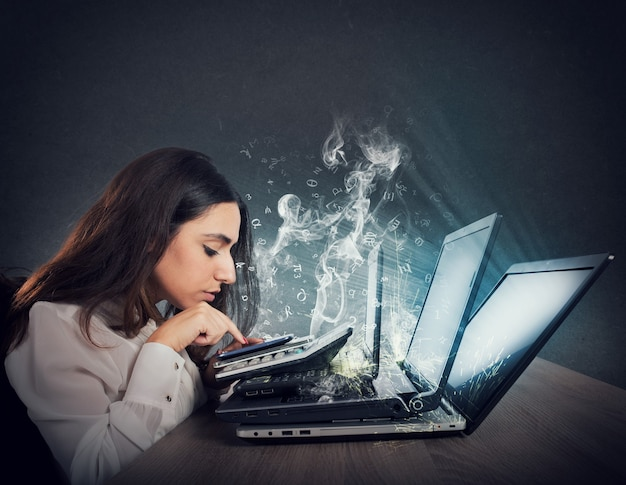 Businesswoman współpracuje z wieloma urządzeniami, smartfonem, kalkulatorem i laptopami. pojęcie przepracowania i stresu