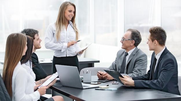 Businesswoman wyjaśniając biznesplan swoim kolegom.zdjęcie z miejscem na tekst