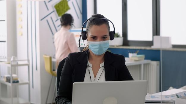 Businesswoman z maską ochronną rozmawiając do mikrofonu siedzi przy biurku tabeli przed komputerem przenośnym. współpracownicy utrzymujący dystans społeczny, aby zapobiegać chorobom wirusowym