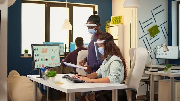 Businesswoman z maską ochronną wyjaśnia afrykańskiemu koledze wykresy ze schowka wskazując na pulpicie komputera, siedząc przy biurku w nowym normalnym biurze. wieloetniczny zespół szanujący dystans społeczny.