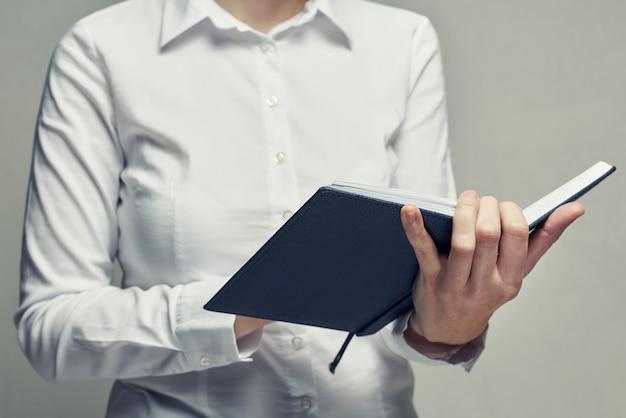 Businesswoman z pamiętnika organizatora w jej ręce