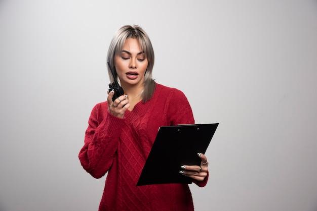 Businesswoman z radiotelefonem patrząc na schowek.
