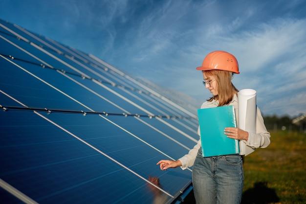 Businesswomen pracuje nad sprawdzaniem sprzętu w elektrowni słonecznej z listą kontrolną tabletu