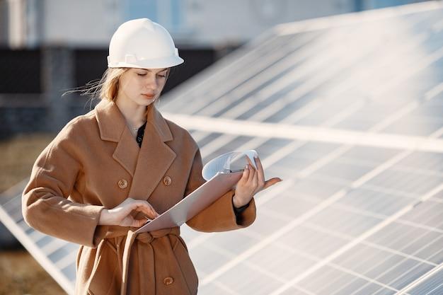 Businesswomen pracuje nad sprawdzaniem sprzętu w elektrowni słonecznej. z listy kontrolnej tabletu, kobieta pracuje na zewnątrz przy energii słonecznej.