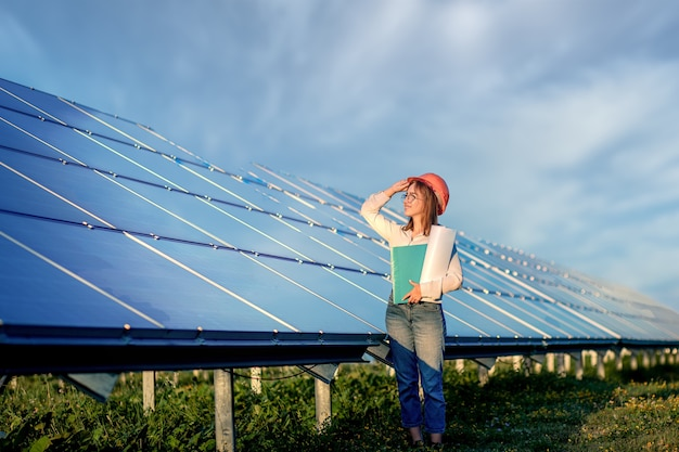 Businesswomen pracuje nad sprawdzaniem sprzętu w elektrowni słonecznej z listy kontrolnej tabletu, kobieta pracuje na zewnątrz w elektrowni słonecznej.