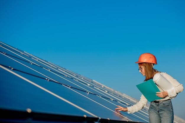 Businesswomen pracuje nad sprawdzaniem sprzętu w elektrowni słonecznej z tabletem