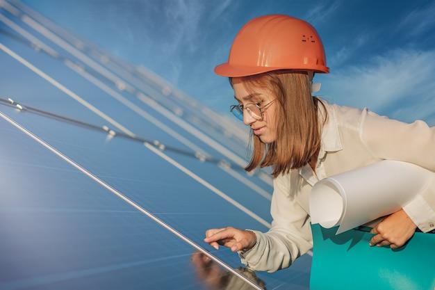 Businesswomen pracuje nad sprawdzaniem sprzętu w elektrowni słonecznej