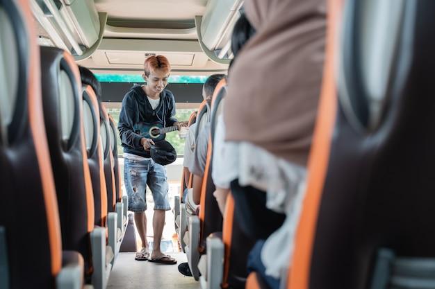 Busker używający instrumentów muzycznych ukulele i kapeluszy, prosząc pasażerów autobusu o pieniądze podczas podróży