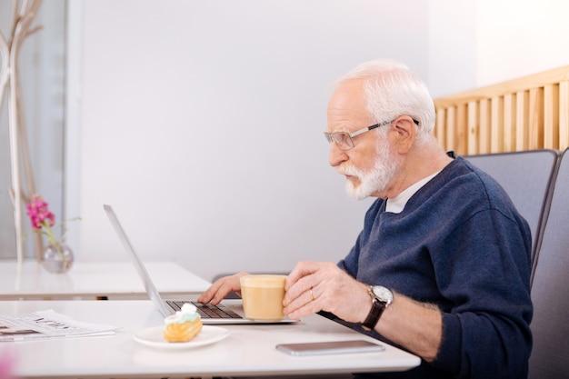 . bussing senior freelancer za pomocą laptopa i pozowanie w profilu