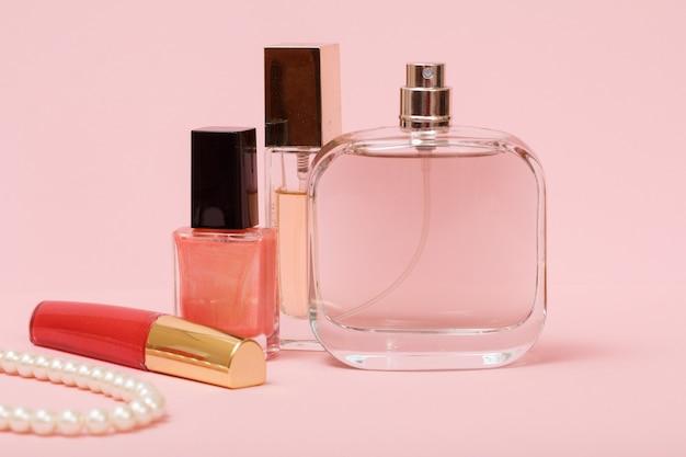 Buteleczki z damskimi perfumami, lakierem do paznokci, szminką i koralikami na sznurku w różowym tle. kosmetyki i akcesoria dla kobiet.