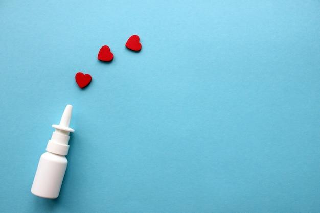 Butelka aerozolu do nosa na niebieskim tle i czerwone serduszka dookoła