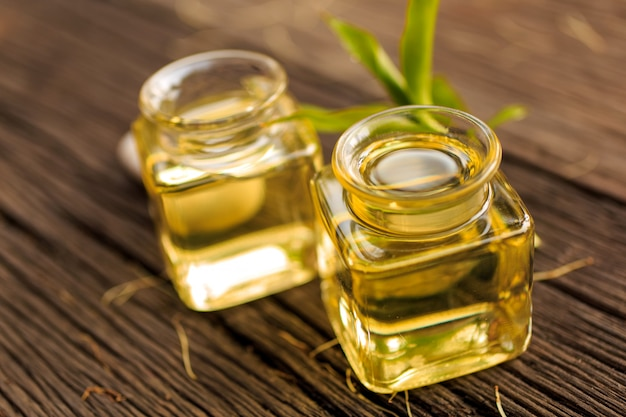 Butelka aromatycznego olejku lub spa i naturalny zielony urlop na drewnianym stole