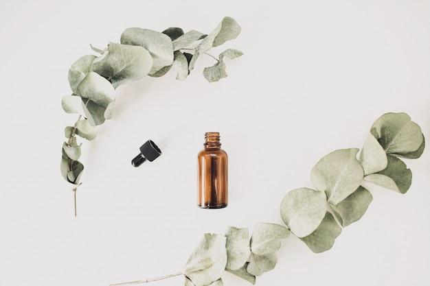 Butelka aromatycznych olejków kosmetycznych lub eterycznych na białym tle, w otoczeniu gałęzi eukaliptusa na białym tle. widok z góry. skopiuj miejsce.
