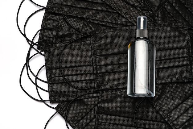 Butelka balsamu, środka odkażającego lub mydła w płynie i medyczne maski ochronne na białym tle