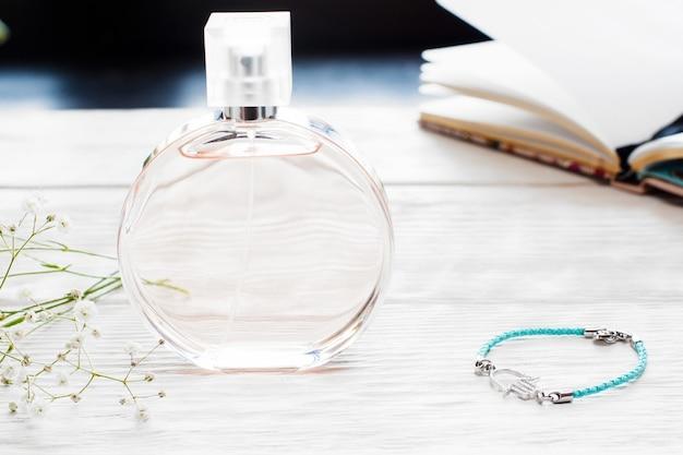 Butelka bezimiennych perfum na stole kobiet z różnymi pracownikami. pamiętnik, ręcznie robiona bransoletka i fiolka z esencją na białym drewnianym stole. kobiece miejsce pracy