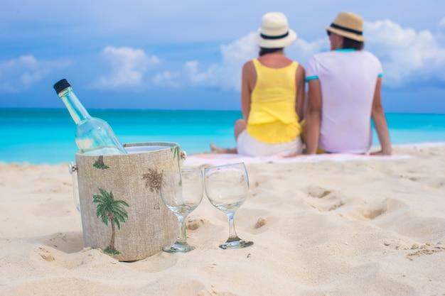 Butelka białego wina i dwa szkieł tła szczęśliwa para na piaskowatej plaży