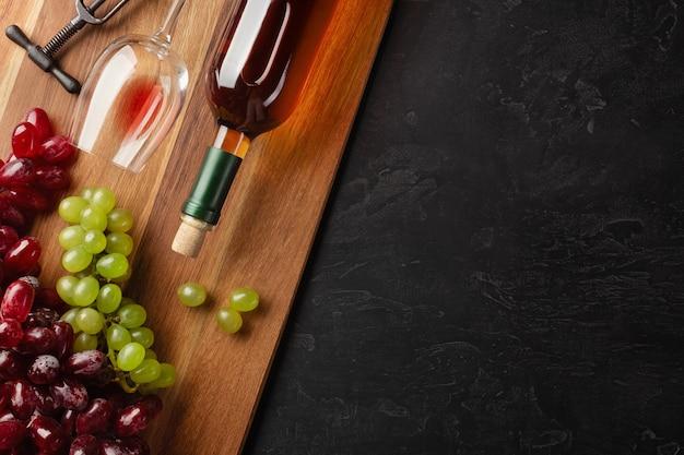 Butelka białego wina, kiść winogron i kieliszek na desce i czarnym tle. widok z góry z miejsca na kopię.