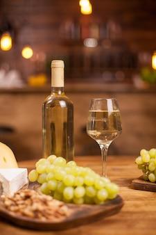 Butelka białego wina pełna kieliszek obok różnych serów. świeże winogrona. smaczne orzechy włoskie.