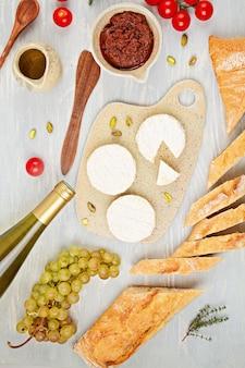 Butelka białego wina, sera, chleba i pomidorów na przyjęcie w formie bufetu. tradycyjny francuski lub włoski wymaga płaskiego układania. widok z góry
