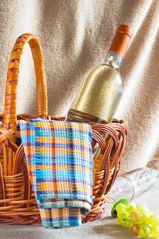 Butelka białego wina, serwetka i kiść winogron w koszu