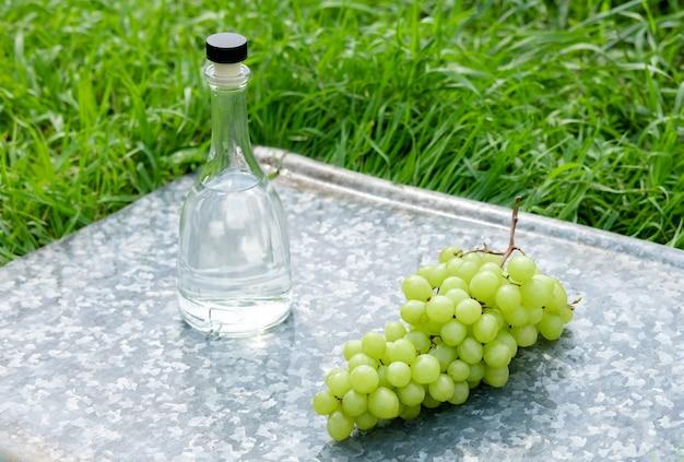 Butelka białego wina, szkło, młode winorośli i kiść winogron na zielonym tle na tacy. letni napój winogronowy
