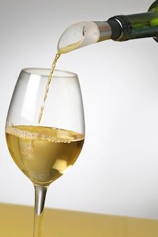 Butelka białego wina w szklance.