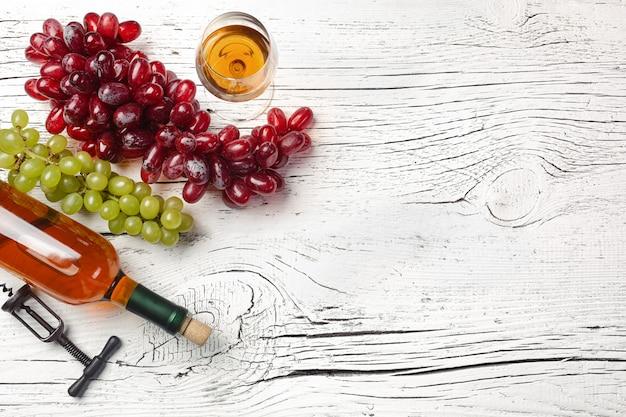 Butelka białego wina, winogron, miód, ser i lampka na tle białej drewnianej tablicy